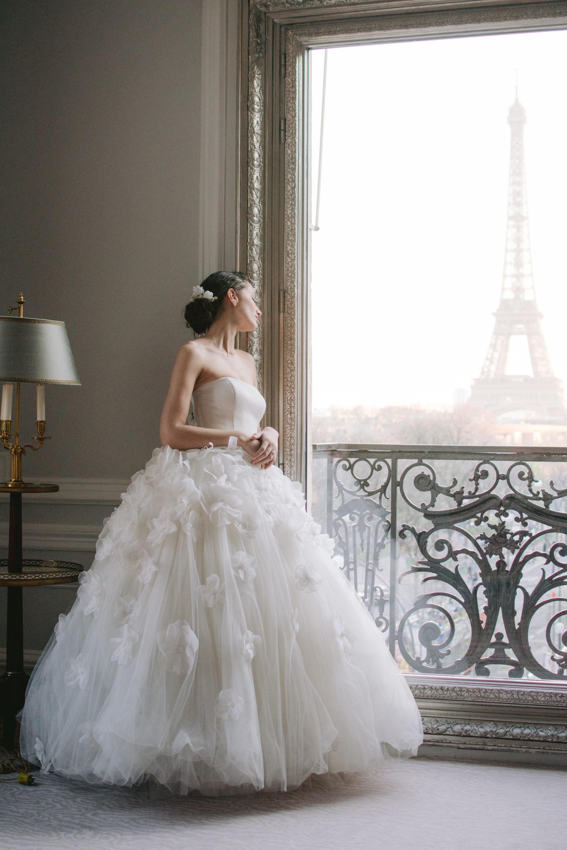 une mariée regarde par le fenêtre et voit la tour eiffel